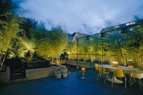 Modern Night Time Garden Scene Feature Glass Covered Seating Area, Pond,  Trees And Potted