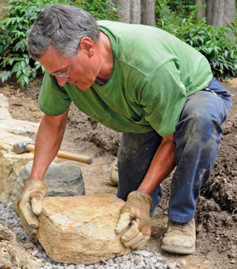 mark smith, foreman of JM Garden design lifting large rock in a garden