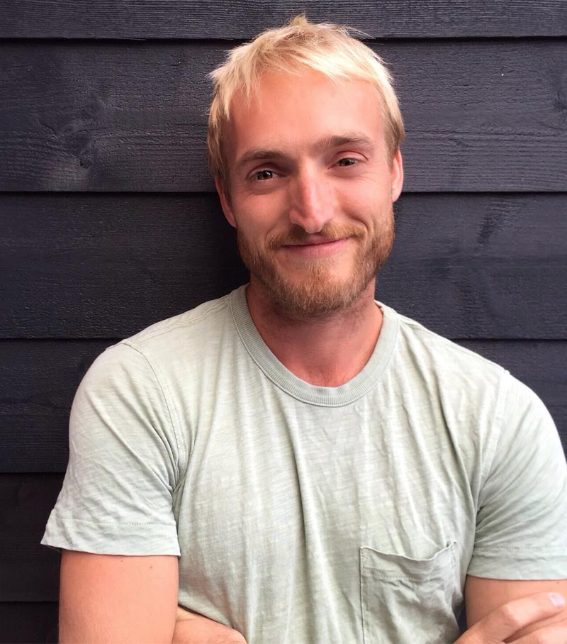 Chris Pike, JM garden designer wearing green t-shirt in front of shed