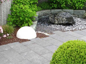 Large stone ewater feature sounded by stone greay stone wall with large white dome light and round tree in foreground