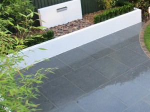 Wet grey granite paving in front of a white wall with modern white water feature pouring water onto large stones and pebbles