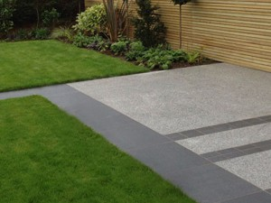 grey granite paving laid out in a modern garden with square green lans and modern light brown fencing