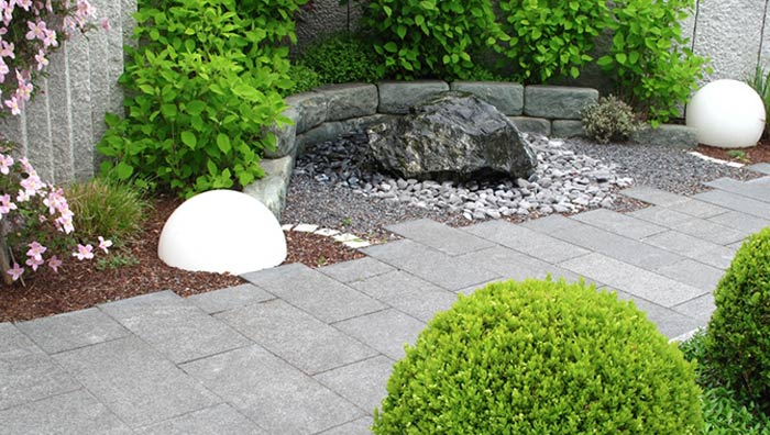 Granite paving with large stone water feature with 2 large done lights at either side