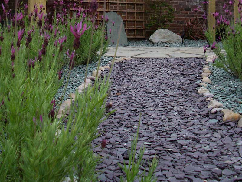 loose stone pathway leading to circular paved area