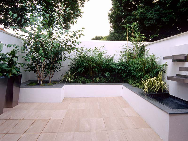 Raised white wall hosting plants, trees and water feature