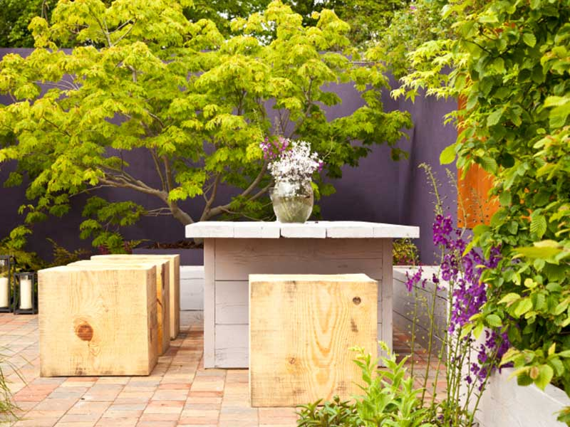 Garden scene with wooden seating blocks and painted wooden table. Bright green trees sourrounding