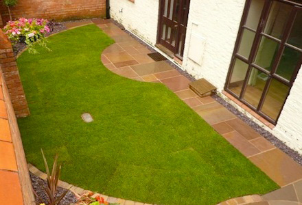 semi circular lawn infront of large window and door leading into the a home