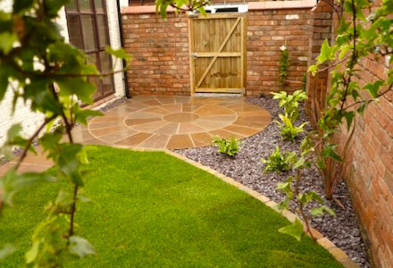 circular paving leading to gate with lawn in the foreground