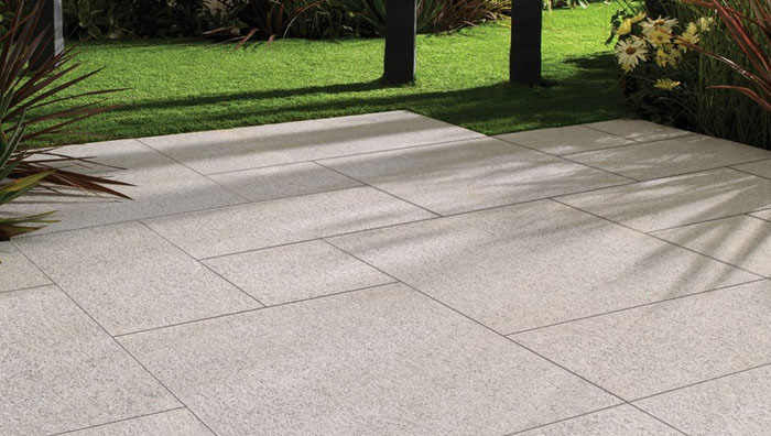 Granite patio laid out with lawn and trees in background