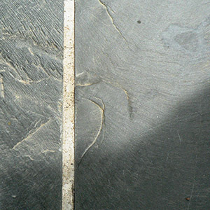 blue grey slate texture in sunlight casting a dark shadow